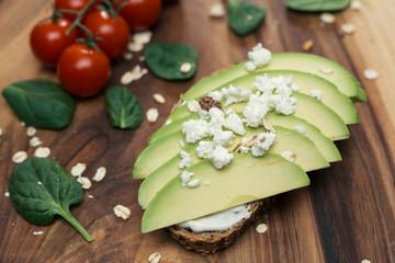 avocado sandwich with feta cheese on wooden board