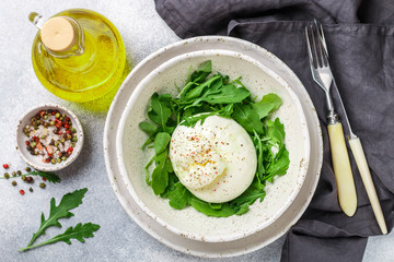 Delicious Creamy Italian Burrata Cheese Served with Olive Oil, fresh arugula and spices in a white plate