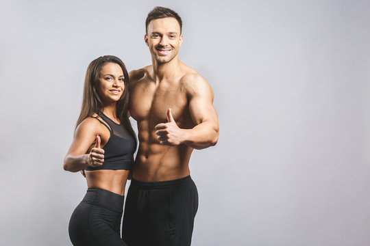 Athletic man and woman isolated over white background. Personal fitness instructor. Personal training. Thumbs up.