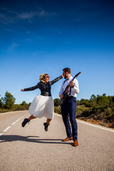 Rock bride with black leather jacket, boots and sunglasses poses with her boyfriend who plays an electric guitar in the middle of a lonely road.