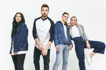Group of smiling friends in fashionable jeans. The young men and woman posing at studio. The fashion, people, happy, lifestyle, clothes concept Wall mural