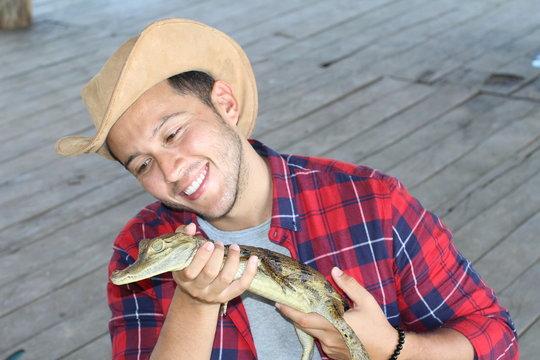 Ethnic man holding baby caiman