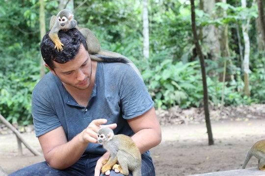 Man training a group of titi monkeys