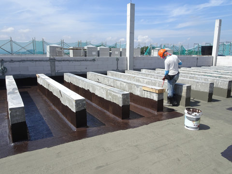 Waterproofing membrane applied by construction workers on top of concrete slab. Waterproofing layer to prevent water from entering below of the concrete slab.