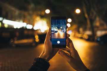 Female's hands holding mobile phone with preview of photograph