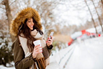 Young woman in a snow park drinks tea