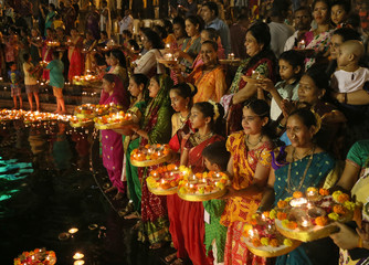 Hindu devotees hold oil lamps as they offer prayers to mark Dev Deepawali festival at the holy Banganga Tank in Mumbai