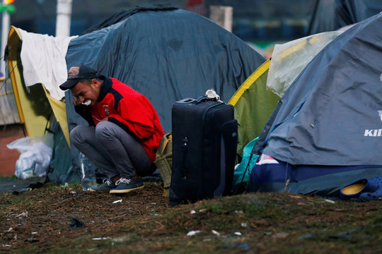 A Venezuelan migrant brushes his teeth outside his tent in a makeshift camp in Bogota