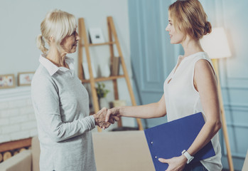 Social worker shaking hands with her elderly client