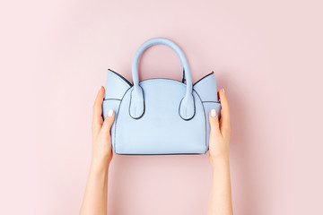 Wall Mural - Female hands holds handbag on pink  background . Flat lay, top view. Spring fashion concept in pastel colored