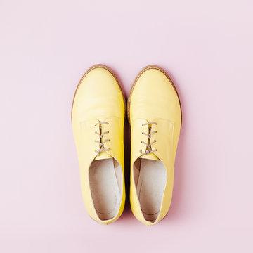 Stylish yellow shoes on pale pink background, flat lay