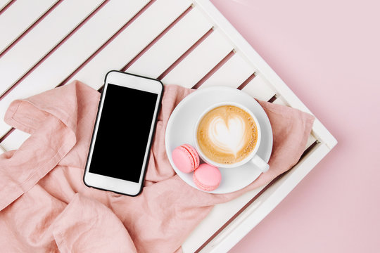 Cup of coffee on white wooden serving tray and Smartphone. Flat lay, top view