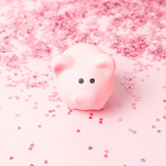 Ceramic toy pink pig symbol of the new year and holographic glitter confetti form of stars on pink background Flat Lay copy space. Decoration Festive decor, celebration Xmas holiday