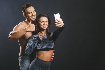 Portrait of beautiful european couple in sports clothes making selfie using a smartphone and smiling while resting after workout.