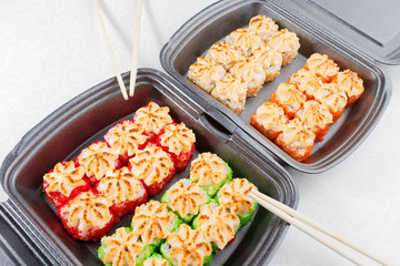 Sushi in plastic packaging. Baked sushi and chopsticks.