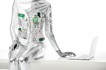 cropped image of robot sitting on table and using laptop isolated on white, future technology concept