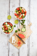 Watermelon salad with feta, cucumber, mint and lime dressing on white wood