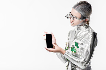 silver robot looking at smartphone with blank screen isolated on white, future technology concept