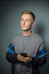 Portrait of young man listening music with earphones and smartphone