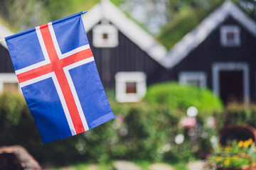 Iceland, Iceland national flag in the foreground, typical icelandic houses with grass on the roof in the background