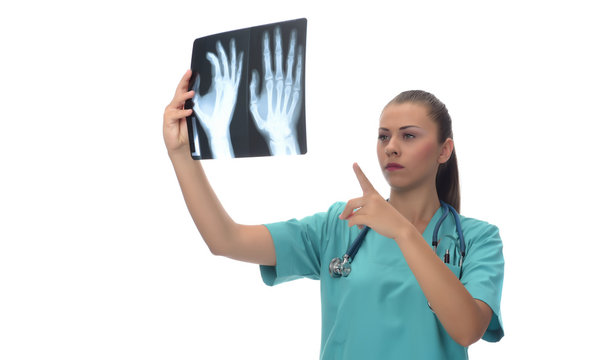 Young female surgeon doctor looking to x-ray , isolated on white