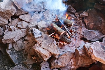 Wood burning in a fire which will eventually turn into coals which will be used to braai (cook) meat.