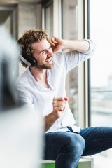 Happy casual young man listening to music with headphones at the window