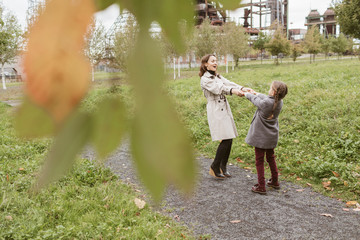 Mother and little daughter dancing together on walkway in autumn