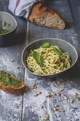 Homemade basil pesto, spaghetti in a bowl, rye baguette on wood