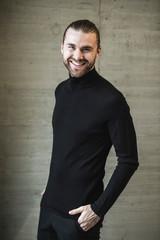 Portrait of smiling young man wearing black turtleneck jumper