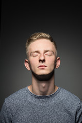 Portrait of blond young man with eyes closed