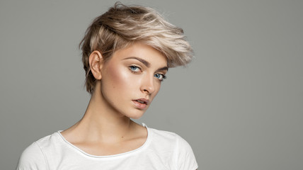 Portrait of young girl with blond short hairstyle looking at camera isolated on gray background with copy space Fototapete