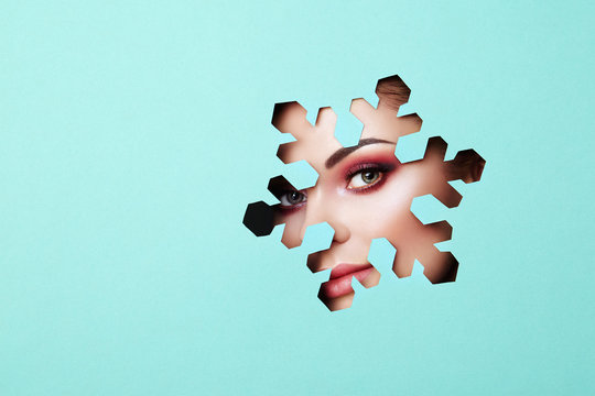 Face of a Young Beautiful Woman with a Beauty Make-up. Extension Eyelashes, Beautiful Green Eyes with Pink Shadows. Snowflake. Christmas Patterns. Blue Paper