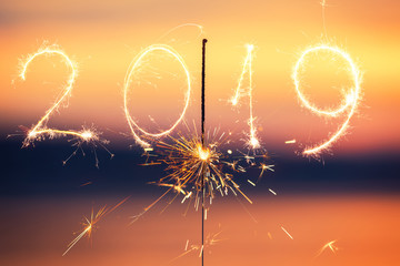 2019 and Happy new year with Sparkle firework on sunset background