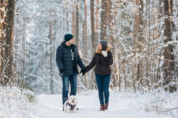 Cute young couple having fun in winter forest with their pretty little white dog. Man and woman in sweater with a snowflake. Christmas and winter holidays