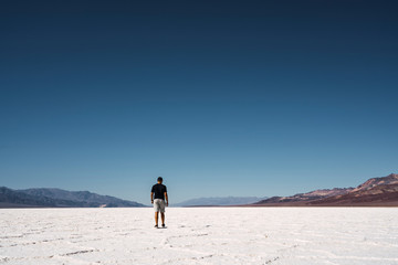 Person walking on white death lands between hills