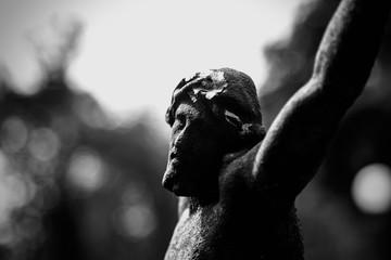 Dramatic silhouette of an old statue  with deep shadows of crucifixion Jesus Christ. Antique sculpture. Religion concept.