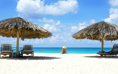 Cabana, parasol. White sand beach. Blue sea water and dramatic clouds. Oranjestad, Aruba. Famous Eagle Beach.  Unidentifiable sun bather.