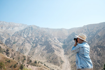 Hiker photographer taking picture of the landscape with mountains