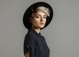 Fashion portrait of female model with blond short hair wear black hat and looking at camera Wall mural