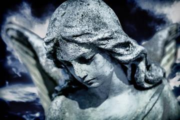 Beautiful sad angel marble sculpture looks down. Pain, religion, faith concept.
