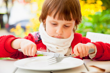 Little cute child girl with a knife and a fork wants to eat and waits for lunch.