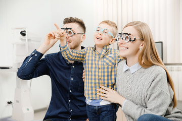 Cheerful family with small child reception doctor ophthalmologist using glasses
