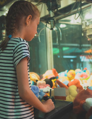 Little girl playing claw crane in theme park.