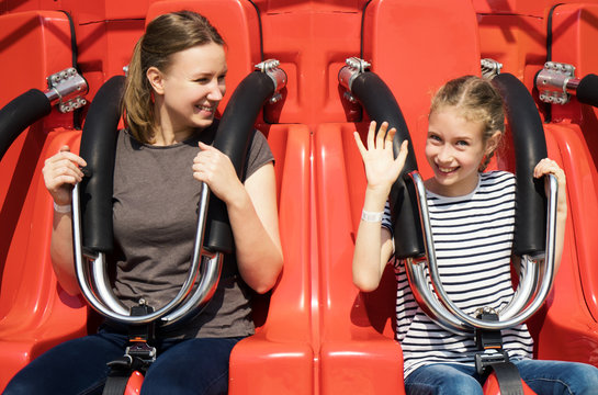 Mom and daughter are sitting on the attraction in the park.