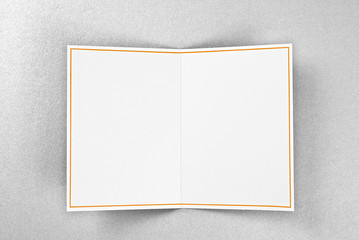 Blank greeting card decorated with gold frame over silver background