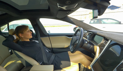 CLOSE UP: Young businesswoman sleeping in self driving car on her drive to work.