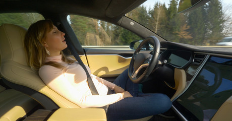 CLOSE UP: Female tourist sleeps while the autonomous car drives her down highway