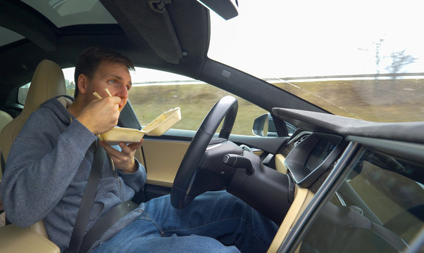 CLOSE UP: Young man eating Chinese food while driving in his high tech car.