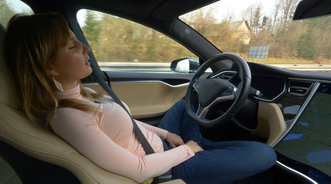 CLOSE UP: Young woman sleeping while her car drives her to her destination.